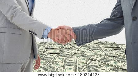 Digital composite of Business people shaking hands with money in background