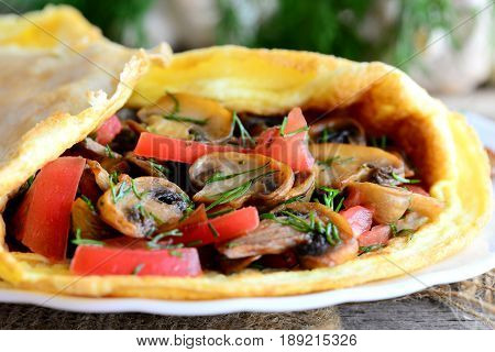 Mushrooms and tomatoes omelet recipe. Home omelet stuffed with fried mushrooms, fresh tomatoes and dill greens on a plate and vintage wooden table. Easy vegetarian omelet recipe. Rustic style