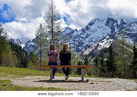 Two woman sitting on bench and watching beautiful mountain view of German Alps. Location: Rossfeldstrasse panorama road near Berchtesgaden, Bavaria, Germany.