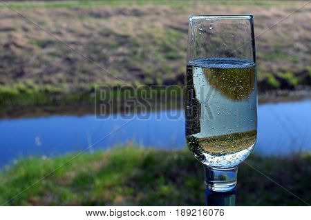 Glass of sparkling wine outdoors. Focus on foreground.