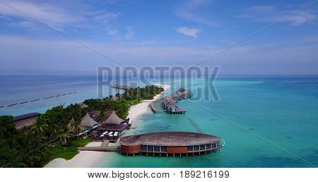 Aerial flying drone view of Maldives white sandy beach on sunny tropical paradise island with aqua blue sky sea water ocean 4k luxury 5 star resort hotel water bungalow hut relaxing holiday vacation.