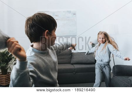 Little Boy And Girl Playing Pillow Fight At Home
