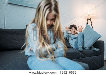 Little Boy In Pajamas Gesturing And Grimacing While Upset Sister Sitting On Couch