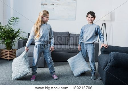 Adorable little children in pajamas having pillow fight at home