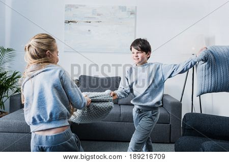 Cute little siblings in pajamas fighting with pillows at home