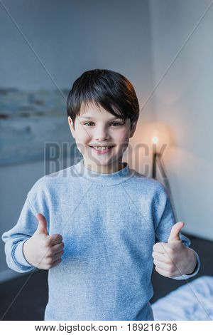 Cute Little Boy Showing Thumbs Up And Smiling At Camera