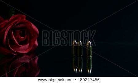 Bullet and red rose the black mirror background