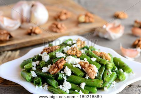 Warm green bean salad. Easy green string beans salad with cottage cheese, peeled walnuts, garlic and spices on a white plate and wooden table. Rustic style. Green bean summer salad for healthy dinner