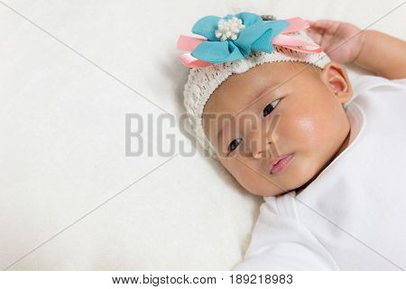 Close - Up Two month old new born asian cute baby rests happily on white bed background.
