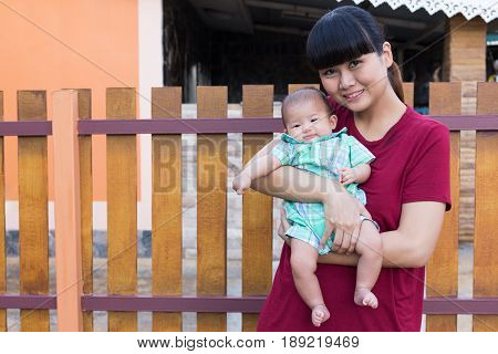 Asian cute new born baby smile happily with holding hands mother in house.