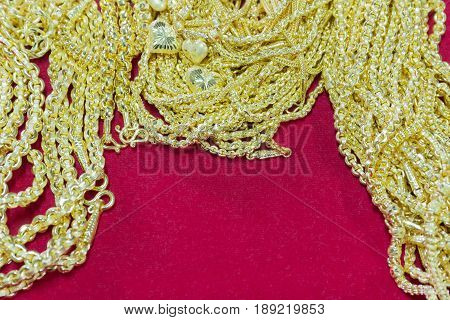 Luxury gold necklace on red flannel copy space background beautiful golds is pendant ornament accessory asian style selection focus.