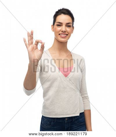 gesture, fashion, portrait and people concept - happy smiling young woman with braces showing ok hand sign over white