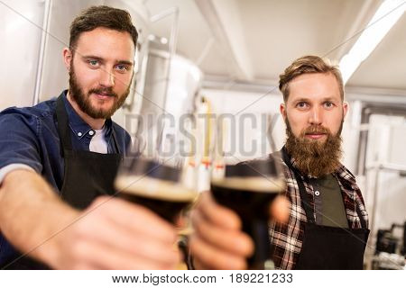 alcohol production, manufacture, business and people concept - men drinking and testing craft beer at brewery