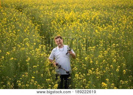 Man on a yellow rapeseed field in the evening at sunset.