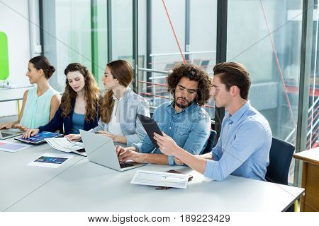 Business team working on laptop and digital tablet in meeting at office
