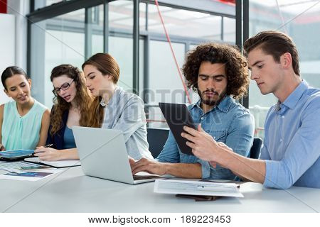 Business team discussing over laptop and digital tablet in meeting at office