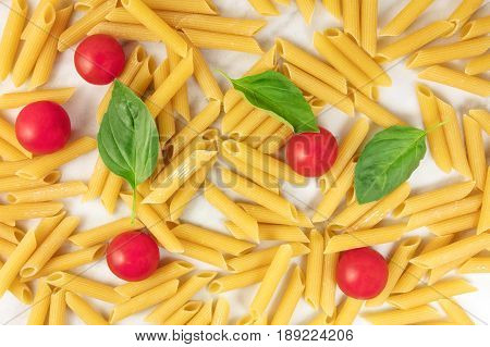 Penne rigate, shot from above on a white marble table. An overhead photo of a texture of pasta, basil leaves, and cherry tomatoes