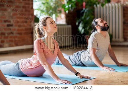 fitness, people and healthy lifestyle concept - man and woman doing cobra pose on mats at yoga studio
