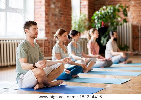 fitness, yoga and healthy lifestyle concept - group of people meditating in lotus pose at studio