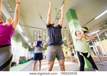 fitness, sport and exercising concept - group of people with medicine balls training in gym and coach writing to clipboard