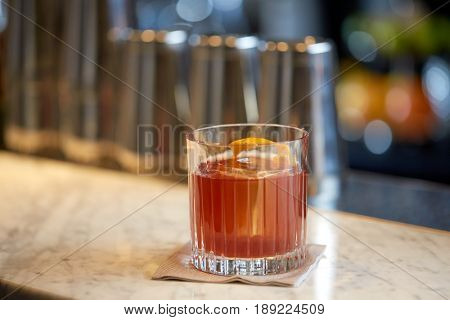 alcohol drinks and luxury concept - glass of cocktail with orange peel at bar
