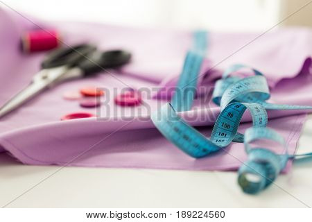 needlework and tailoring concept - scissors, sewing buttons, tape measure and cloth
