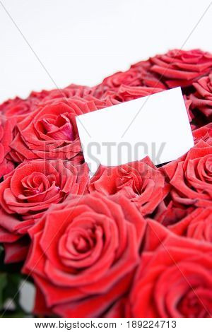 A bouquet of roses with a business card