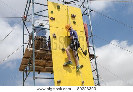 Boy With Safety Equipment Climb On Yellow Climbing Wall