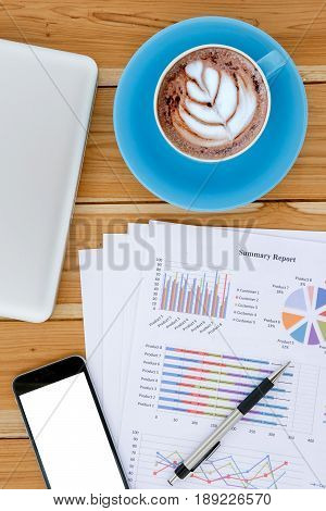 Portrait office desk table with pencilblank screen smartphonelaptopchart or graph over backboard and cup of coffee.Top view