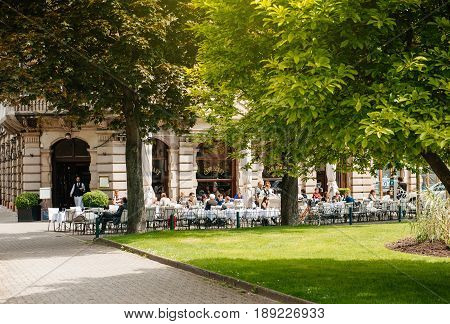 STRASBOURG FRANCE - MAY 18 2017: French people and tourists enjoying a cafe and a dessert outside terrace cafe Brant in Strasbourg France