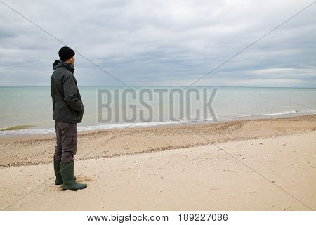 male in green jacket and knee-high boots standing on the beach and looking at the sea. Green sea water thunderclouds on the background