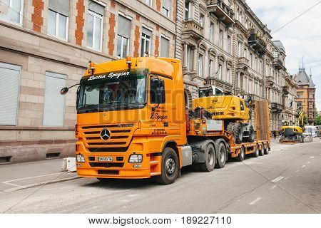 STRASBOURG FRANCE - MAY 18 2016: Mercedes-Benz Actros 2660 truck transporting construction excavator at the construction site in urban environment during roadwork