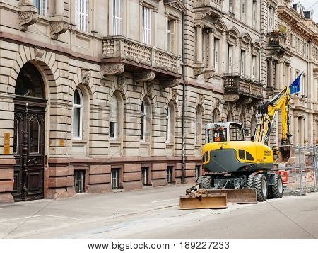 STRASBOURG FRANCE - MAY 18 2016: Wacker Neuson Yellow excavator working in urban environment with luxury apartment office historic building behind