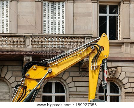 Detail of modern excavator working in city - rebuilding the neighborhood building houses with powerful boom and hydraulic cylinder