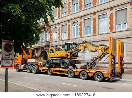 STRASBOURG FRANCE - MAY 18 2016: Liebherr 912 compact excavator on transportation trailer in urban environment with luxury apartment office historic building behind