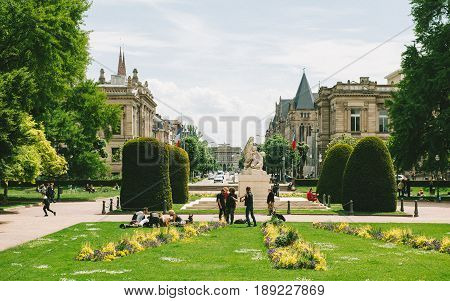 STRASBOURG FRANCE - MAY 18 2016: People having fun in Place de la Republique Park near the Palais du Rihn Palace of the Rhine the former Kaiserpalast (Imperial palace) with Avenue de la Liberte and and University of Strasbourg building in the background