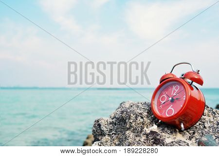 Red alarm clock on rock and sea background concept time to travel holiday summer season