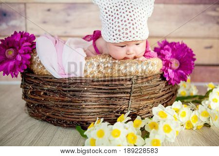 The baby lies in a basket with yellow daffodils and gerberas on a wooden background