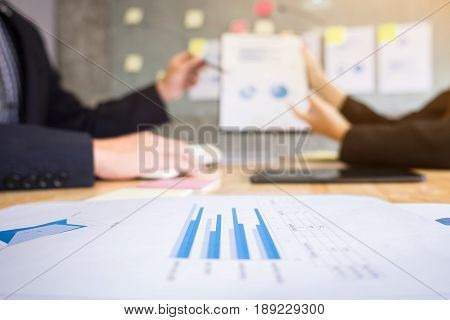 business women and secretary presentation report two colleague excultive conference presentating chart report of new plan marketing to development consultating business in company blurred background.