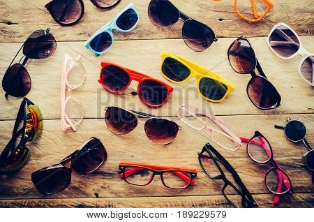 Many sun glasses fashion and eyeglasses on the wood