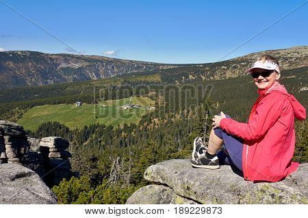 A girl in a red jacket sitting on rocks in the Czech mountains