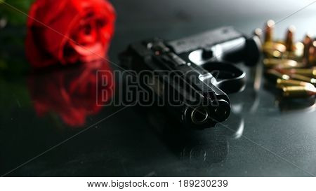 Black hand gun and bullets on the black mirror background.