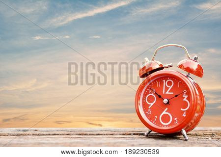 alarm clock on table and sunset on the seaside background