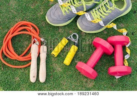 fitness concept with Exercise Equipment on green grass background.