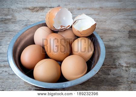 egg shell and fresh eggs in Metal cup on wooden background.