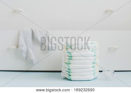 A stack of diapers on the background of a white dresser with linen