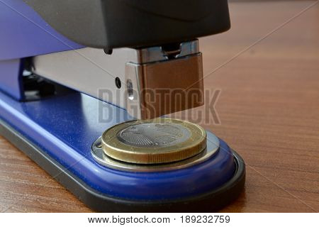 Business background with table stapler and coin.