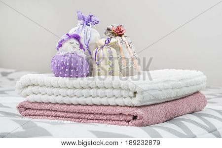 Scented sachets and purple lavender pouch figure of a girl. Nice smelling bags in bedroom. Towels on bed. Decoration, furnishing and storage items. Aromatic potpourri at home.