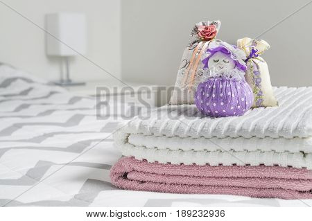 Scented sachets and fragrant pouch figure of a girl. Bags filled with lavender in bedroom. Towels on bed. Decoration accessories and light color Scandinavian interior design. Aromatic potpourri.