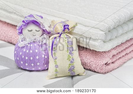 Lavender sachet and scented pouch figure and character representing a girl or woman. Close up to dried lavender in decoration bags in bedroom and towels on bed. Aroma potpourri and storage items.